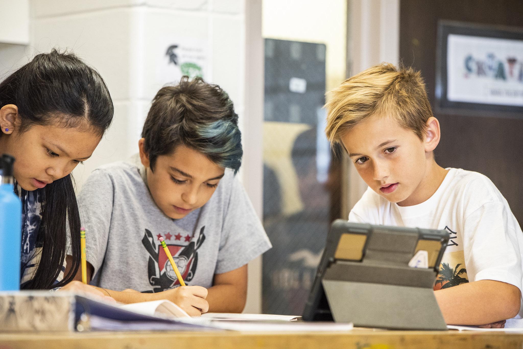 three students working on an ipad